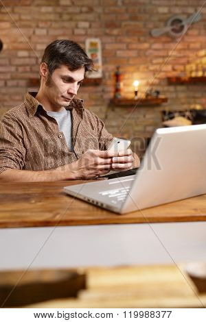 Casual young man using mobilephone, texting, sitting at desk, having laptop.