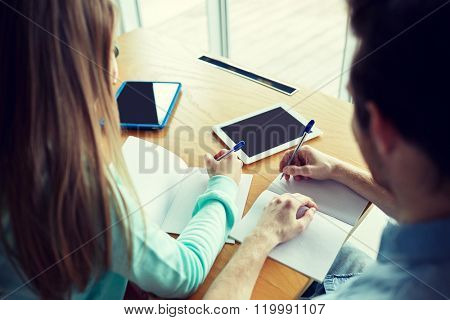people, knowledge, education and school concept - close up of students with tablet pc computers sitting at table and writing to notebooks