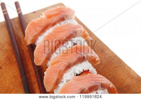 classic onigiri inside out californian sushi rolls with salmon on wooden plate isolated over white background with sticks