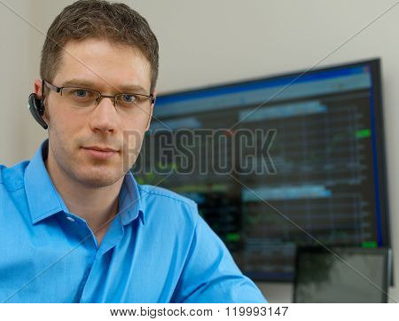 Handsome stock trader in front of computer.