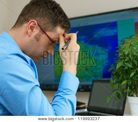 Handsome male meteorologist in glasses thinking ove map background