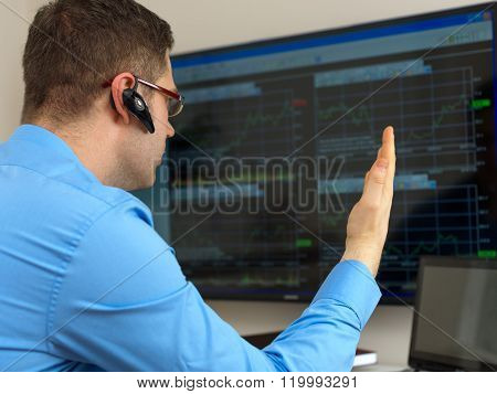 Angry stock trader in front of computer.