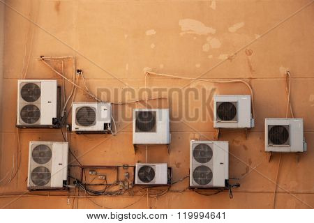 many air condition machines on a brown wall