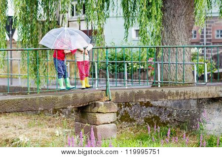 Two little kid boys with big umbrella outdoors