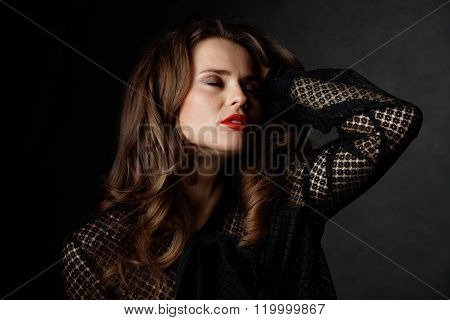 Woman With Long Wavy Brown Hair Posing Against Dark Background