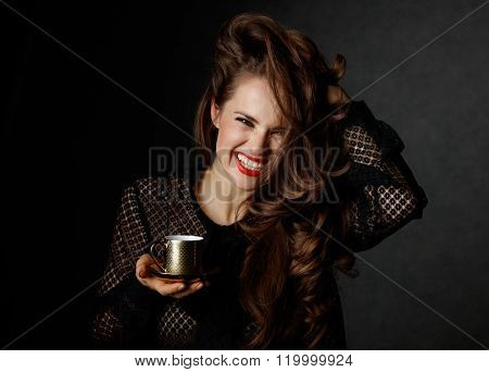 Cheerful Woman Holding Cup Of Coffee On Dark Background