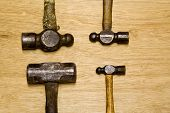 foto of peen  - four old hammers showing hard use on brown background - JPG