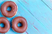 Постер, плакат: Three Crispy Cream Filled Chocolate Donuts