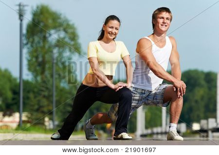 Young fitness couple of man and woman doing physical stretching exercises before jogging sport outdoors
