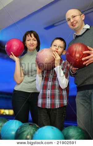 Mother, father and son, stand alongside and hold balls for bowling, focus on father and son