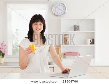 Attractive brunette woman holding a glass of orange juice while relaxing with her laptop in the kitchen