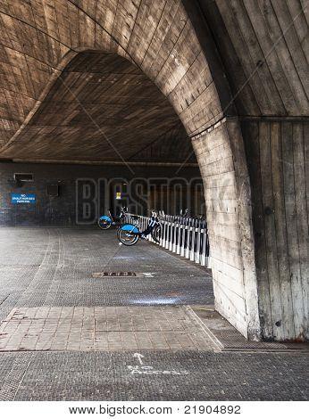 Public rental bicycle station under a bridge in London, UK