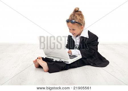 Little girl playing career woman role working on laptop dressed in large suit