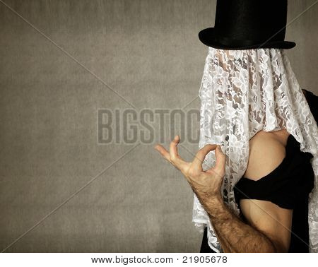 Fantastical stylized portrait of mystery man making a hand gesture  in top hat with lace covering his face