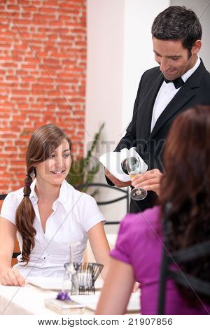 wine waiter pour out wine for customers at a restaurant
