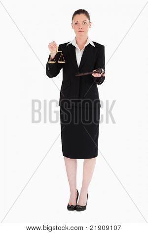 Charming woman in suit holding scales of justice and a gavel while standing against a white background