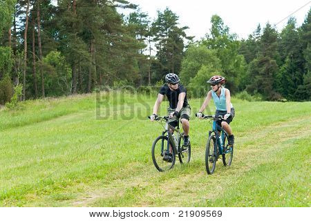 Sport Happy Couple Riding Bicycles In Coutryside