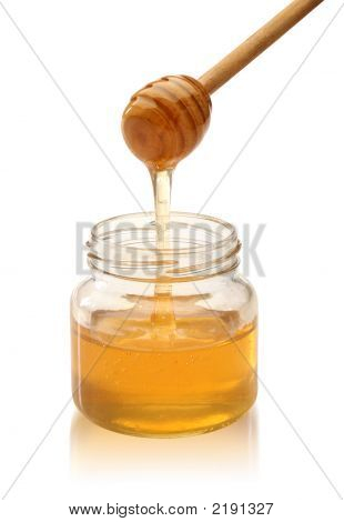 Honey With Wood Stick Pouring.