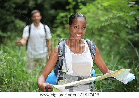 Woman map reading while hiking through long grass