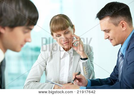 A businesswoman sitting in deep thought among her colleagues