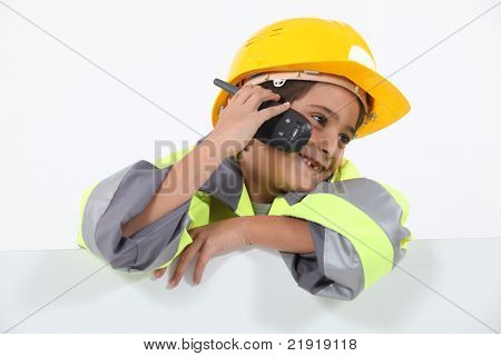 a little boy dressed in road man with a cell phone