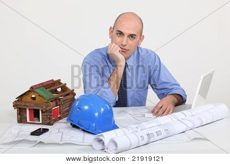 Architect with plans and model of a log cabin