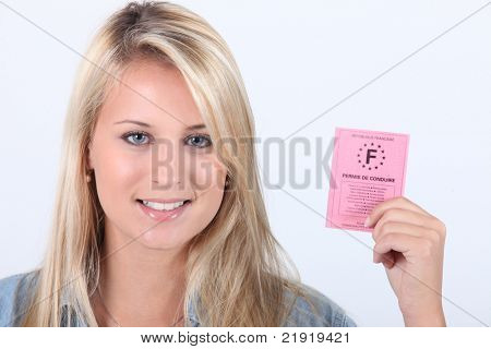 Young woman holding up a French driving license