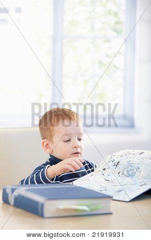 Gingerish Kind studieren Cyclopaedia zu Hause sitzen am Tisch.?