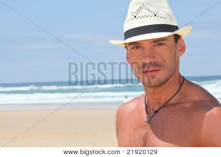 Dude in a straw hat on a sunny beach
