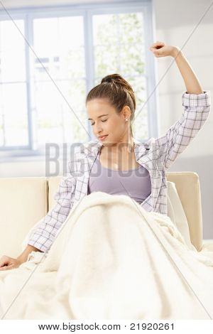 Young woman stretching in pyjama, sitting on sofa, smiling with closed eyes.?