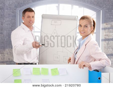 Young people working together in office, using whiteboard, smiling.?