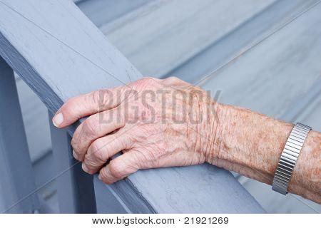 Senior lady sosteniendo el carril de la escalera