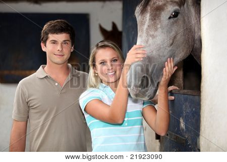 Young couple stood by horse