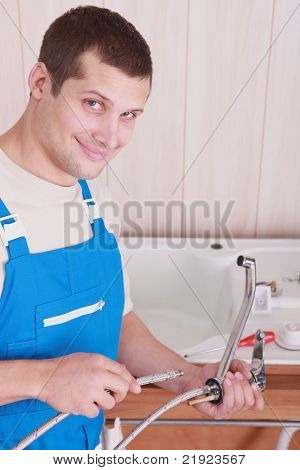Plumber fitting a kitchen tap