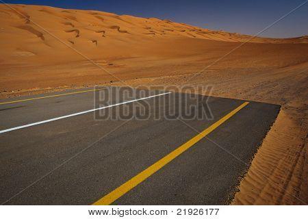 Modernity versus nature concept - end of civilisation, beginning of desert. Modern paved highway ending up in sand dunes.