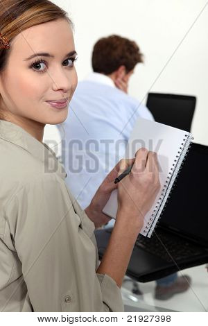 Female university student taking note in lecture
