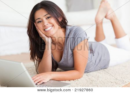 close up of a cute woman lying on a carpet with notebook in living room
