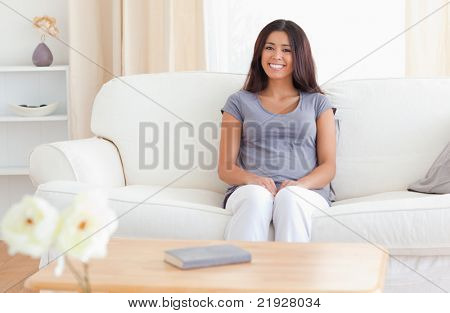 smiling woman sitting on a sofa, there is a table in front of her with a book and flowers on it in the living room