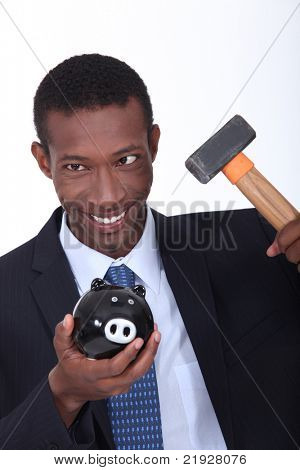 Man hammering open a piggy bank