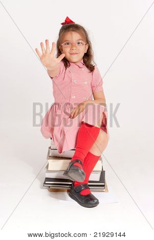 Little girl with glasses and an stopping gesture sitting on a pile of books