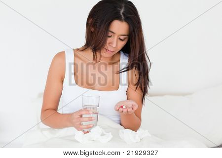 brunette woman having a cold sitting in bed taking pills in bedroom