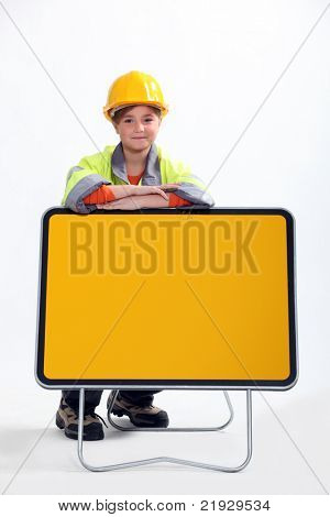 little child dressed in road man is leaning against a yellow road sign panel
