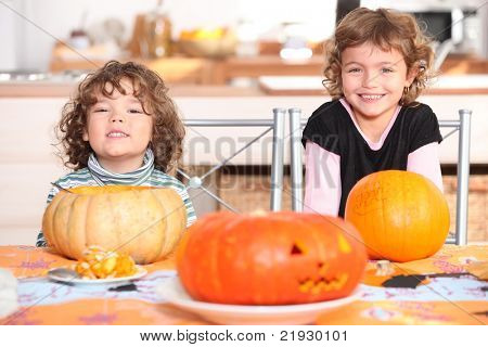 little boy and girl dressed in pajamas posing behind pumpkins