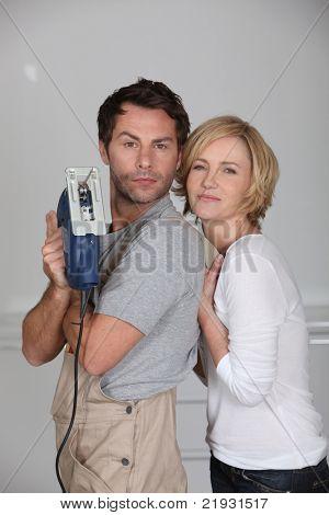 Couple brandishing an electric jigsaw