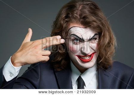Portrait of businessman with theatrical makeup holding fingers at temple