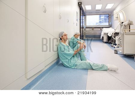 Two young doctors sitting in corridor tired after operation