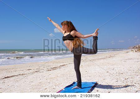 Woman Doing Yoga Exercise Dancer Pose On Beach