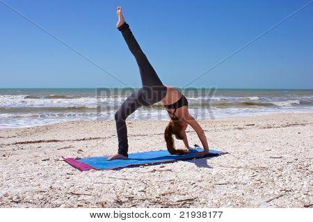 Woman Doing Yoga Exercise One Leg Full Wheel Pose On Beach