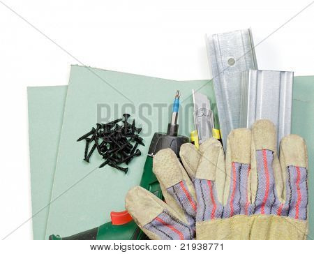 Plasterboard tools set with metal studs, screws, screwgun, cutter and protective gloves on white background