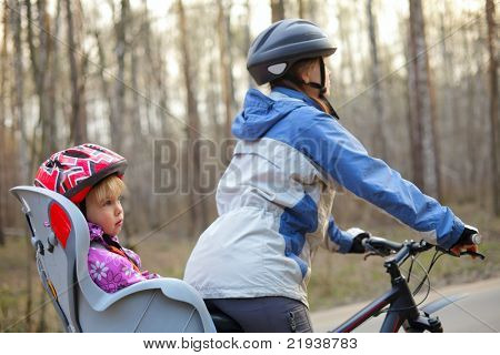 Mother riding on a bicycle with little girl, focus on child